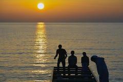 Adolescentes que juegan en el embarcadero en puesta del sol Fotos de archivo libres de regalías
