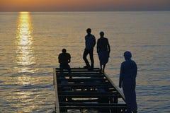 Adolescentes que juegan en el embarcadero en puesta del sol Imagen de archivo libre de regalías
