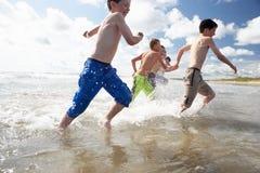 Adolescentes que juegan en la playa Imagen de archivo