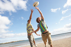Adolescentes que juegan a rugbi en la playa Imagenes de archivo