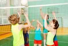 Adolescentes que juegan a voleibol en gimnasio de la escuela Fotos de archivo libres de regalías