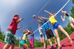 Adolescentes que juegan a voleibol en la corte del juego Imagen de archivo libre de regalías