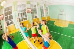 Adolescentes que juegan a voleibol en pasillo de deportes Fotos de archivo