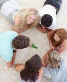 Adolescentes que juegan vuelta la botella en el suelo Imagenes de archivo
