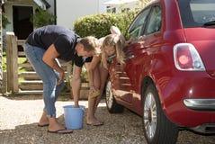 Adolescentes que lavan un coche Fotos de archivo libres de regalías