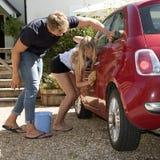 Adolescentes que lavan un coche Foto de archivo libre de regalías