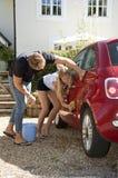 Adolescentes que lavan un coche Imagenes de archivo