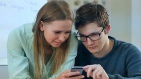 Adolescentes que leem algum índice no smartphone que os faz sorrir Imagem de Stock