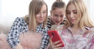Adolescentes que leen el contenido social de los medios en el teléfono móvil almacen de metraje de vídeo