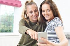 Adolescentes que leen el mensaje de texto en el teléfono móvil Fotos de archivo