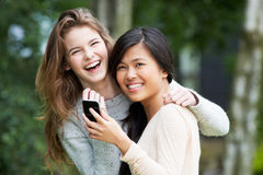 Adolescentes que leen el mensaje de texto junto Fotografía de archivo