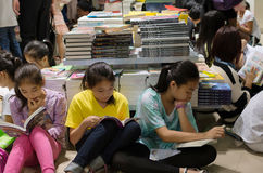 Adolescentes que leen en librería apretada Fotografía de archivo libre de regalías