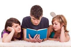 Adolescentes que leen un libro Imagenes de archivo