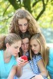 Adolescentes que leen un mensaje del SMS Imágenes de archivo libres de regalías