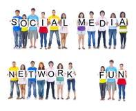 Adolescentes que llevan a cabo carteles para formar la medios diversión social de la red Foto de archivo libre de regalías