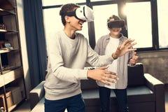 Adolescentes que llevan las auriculares de la realidad virtual en casa Imágenes de archivo libres de regalías