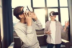 Adolescentes que llevan las auriculares de la realidad virtual en casa Foto de archivo
