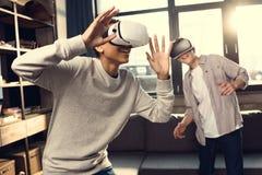 Adolescentes que llevan las auriculares de la realidad virtual en casa Fotos de archivo libres de regalías