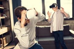 Adolescentes que llevan las auriculares de la realidad virtual en casa Foto de archivo libre de regalías