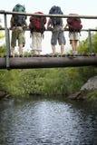 Adolescentes que llevan las mochilas en el puente que mira abajo Imagen de archivo libre de regalías