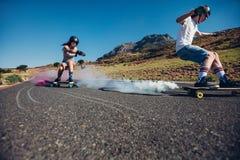Adolescentes que longboarding na estrada aberta Imagens de Stock Royalty Free