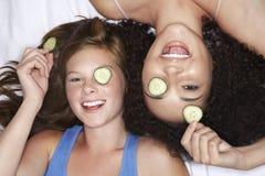 Adolescentes que mienten con los pepinos sobre ojos Imágenes de archivo libres de regalías