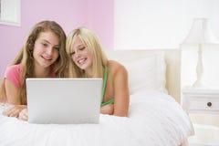 Adolescentes que mienten en cama usando la computadora portátil Imágenes de archivo libres de regalías