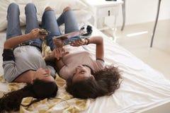 Adolescentes que mienten en cama usando la tecnología, visión elevada Imagenes de archivo