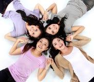 Adolescentes que mienten en el piso blanco Foto de archivo libre de regalías