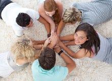 Adolescentes que mienten en el suelo con las manos junto Fotos de archivo libres de regalías