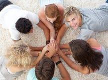 Adolescentes que mienten en el suelo con las manos junto Imagen de archivo libre de regalías