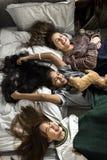 Adolescentes que mienten en la cama así como niñez del peluche y concepto de la amistad Fotos de archivo