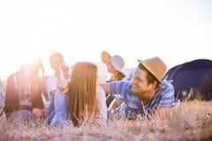 Adolescentes que mienten en la tierra delante de las tiendas Imagen de archivo libre de regalías
