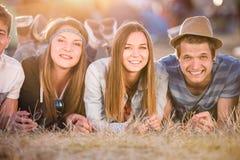 Adolescentes que mienten en la tierra delante de las tiendas Imagen de archivo