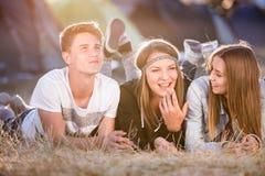 Adolescentes que mienten en la tierra delante de las tiendas Foto de archivo
