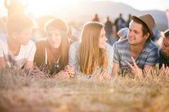 Adolescentes que mienten en la tierra delante de las tiendas Fotos de archivo libres de regalías