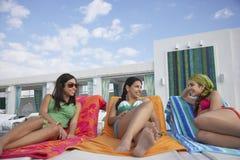 Adolescentes que mienten en Sunloungers en el centro turístico Fotografía de archivo