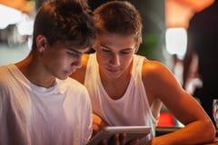Adolescentes que miran algo en la almohadilla táctil Foto de archivo libre de regalías