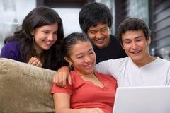 Adolescentes que miran algo en la computadora portátil Imagen de archivo libre de regalías