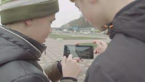 Adolescentes que miran el vídeo que anda en monopatín en el teléfono metrajes