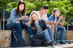 Adolescentes que miran sus teléfonos en parque Imagen de archivo
