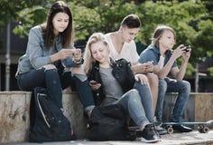 Adolescentes que miran sus teléfonos en parque Fotografía de archivo libre de regalías