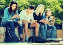Adolescentes que miran sus teléfonos móviles Fotos de archivo