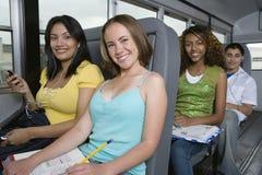 Adolescentes que montan el autobús escolar Imagenes de archivo