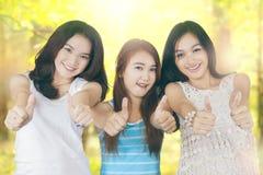 Adolescentes que muestran los pulgares para arriba en naturaleza Imagen de archivo libre de regalías
