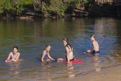 Adolescentes que nadan la laguna de la playa Fotografía de archivo