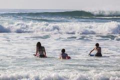 Adolescentes que nadan ondas que practican surf Fotos de archivo