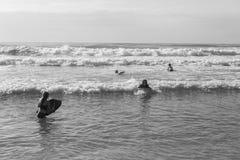 Adolescentes que nadan ondas que practican surf Imagen de archivo libre de regalías