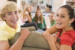 Adolescentes que penduram para fora na frente da televisão Fotografia de Stock Royalty Free