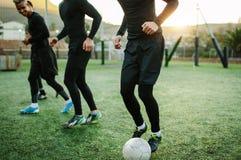 Adolescentes que practican fútbol en campo Imagen de archivo libre de regalías